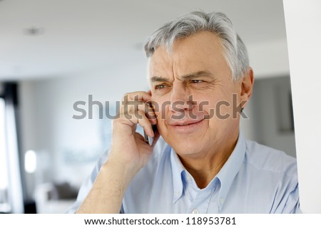 Aged man talking on mobile phone - stock photo