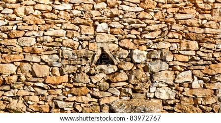 aged masonry stone wall triangle window hole Mediterranean Spain architecture - stock photo