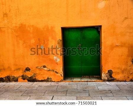 Aged metal door on orange wall / Door / Background / Wall / Barcelona, Spain, Europe - stock photo