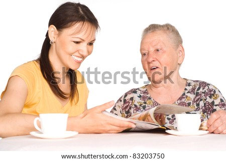 aged mom with her adult daughter at table - stock photo