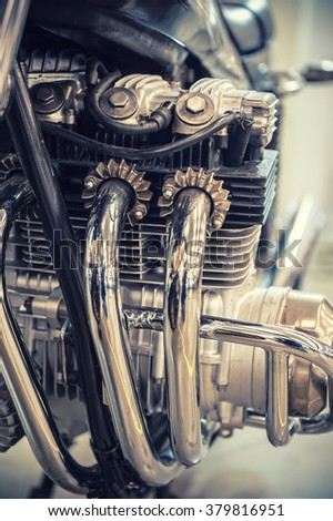 Aged motorcycle engine detail with chrome exhaust pipe - stock photo