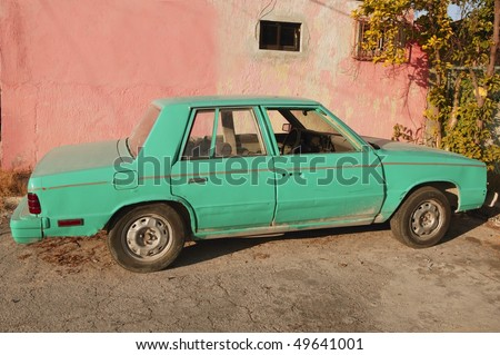 aged old vintage green car in pink wall Cancun Mexico - stock photo