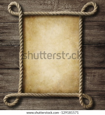 aged paper with rope frame on old wood background - stock photo