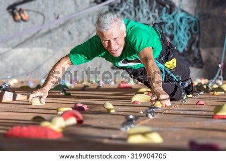 Aged Person Practicing Extreme Sport Portrait of Mature Male Climber Moving Up on Outdoor Climbing Wall Sporty Clothing on Fitness Training Intense but Positive Face Using Rope and Belaying Gear - stock photo