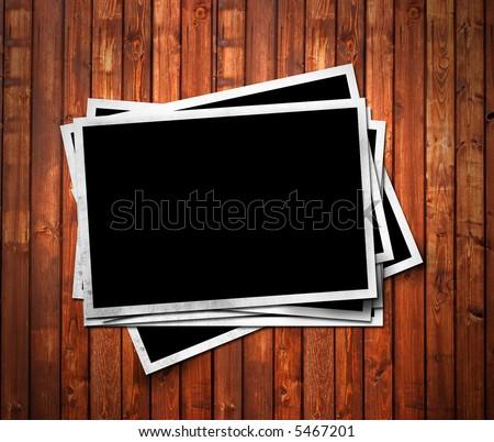 Aged photo frames on wood background - stock photo