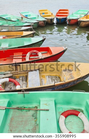 Aged plastic multicolored row boats moored in a lake.