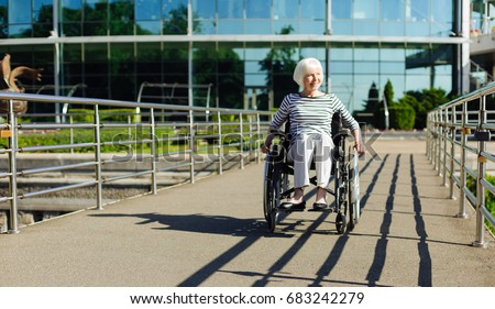 Aged positive woman taking a daily promenade