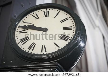 Aged railway station clock with Roman numerals. Horizontal - stock photo