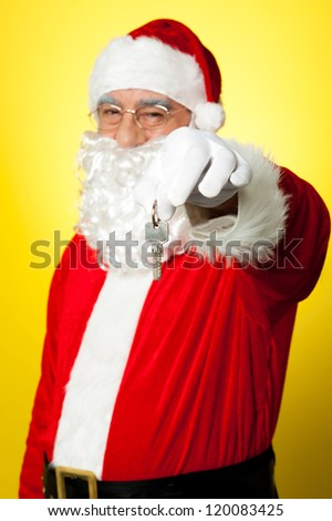 Aged Santa dangling a key. Unlock your X-mas gifts now. - stock photo