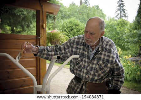 aged senior man with expressive face painting carefully  a garden  table - stock photo