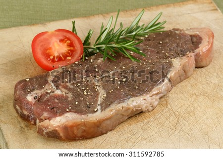 aged sirloin steak uncooked with rosemary and tomato - stock photo