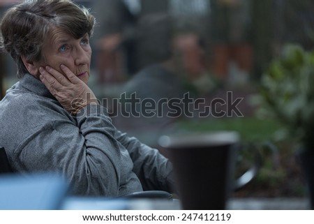 Aged sorrowful woman thinking about old times - stock photo