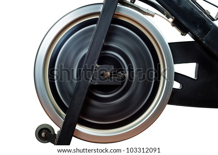 Aged Spinning Bike front detail with Flywheel Rotating. Long Exposure photography on a white background - stock photo