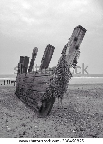 Aged timber breakers on beach look like hull of ship wreck - stock photo
