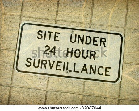 aged vintage photo of 24 hour surveillance sign