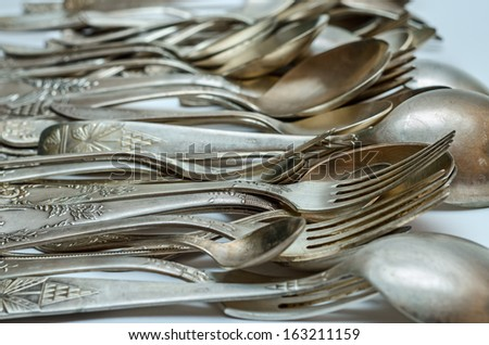 Aged vintage silver cutlery close-up (forks, spoons)