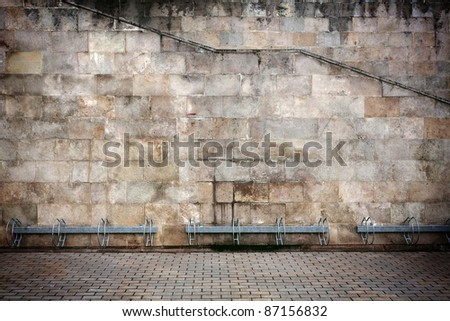 Aged wall with bike stands - stock photo