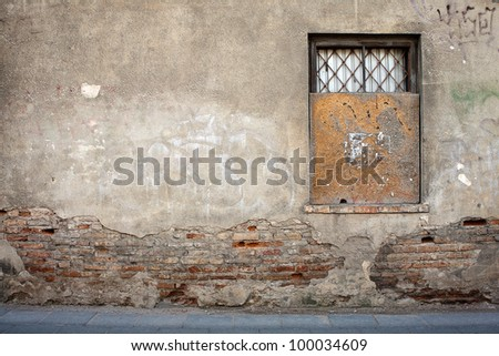 Aged weathered street wall with a window - stock photo