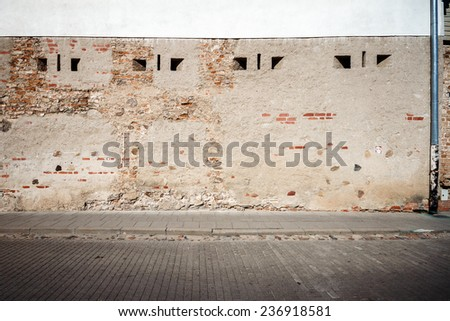 Aged weathered street wall with some small windows - stock photo