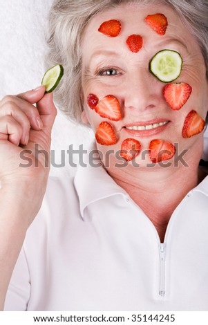Aged woman holding cucumber slice by her eye and looking at camera