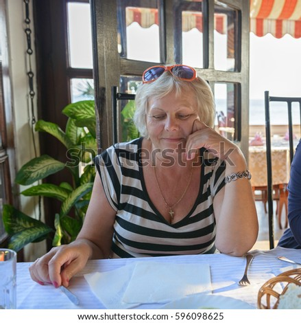 Aged woman is waiting for dinner dishes in resort cafe.