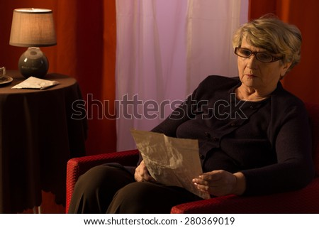 Aged woman reading the letter in her lonely evening - stock photo