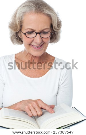 Aged woman relaxing and reading a book