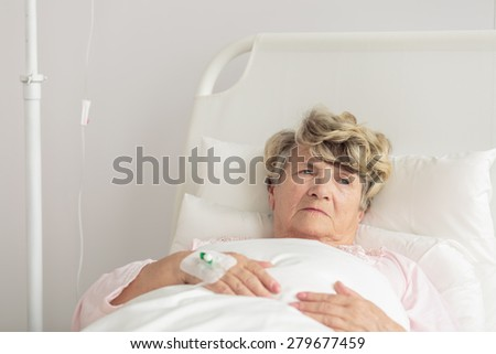Aged woman with intravenous cannula lying in bed - stock photo