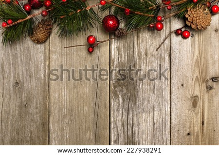 Aged wood Christmas background with branches and baubles top border