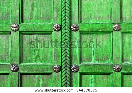 Aged wooden bright green door  with metal bronze rivets on the  wooden textured surface - architectural textured background - stock photo