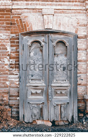 Aged wooden door in the wall of old building in Astrakhan, Russia