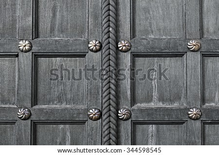 Aged wooden grey door  with metal bronze rivets  - architectural textured background - stock photo