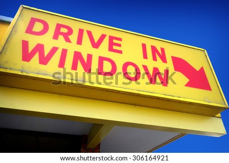 aged worn vintage drive in window sign on building                                - stock photo