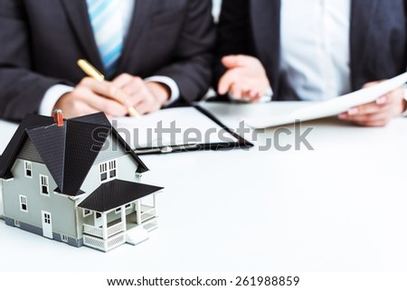Agency. Businessman signs contract behind home architectural model - stock photo