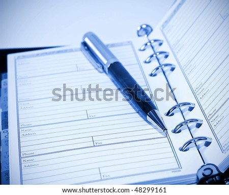 agenda and ball pen. blue toning - stock photo