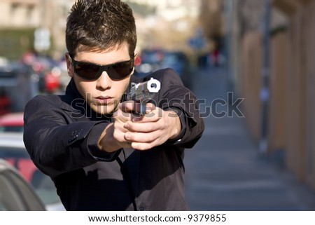Agent aiming with gun in the middle of the street - stock photo