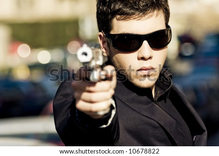 Agent aiming with gun in the middle of the street. Weapon out of focus. - stock photo