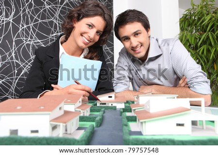 Agent and client looking at a new-build property model - stock photo