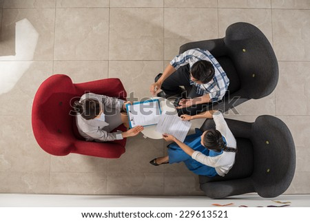 Agent and couple discussing real estate sale contract, view from the top - stock photo