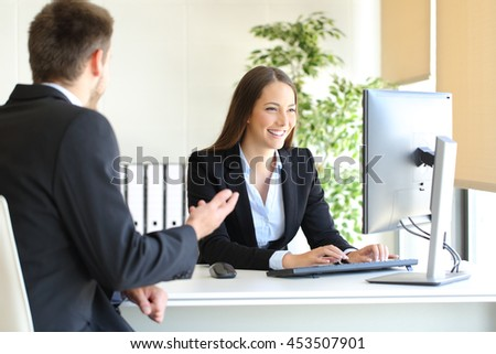 Agent attending to a client introducing data in a desktop computer at office - stock photo