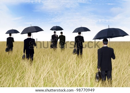 agent concept: businessmen with umbrella ready to give protection - stock photo