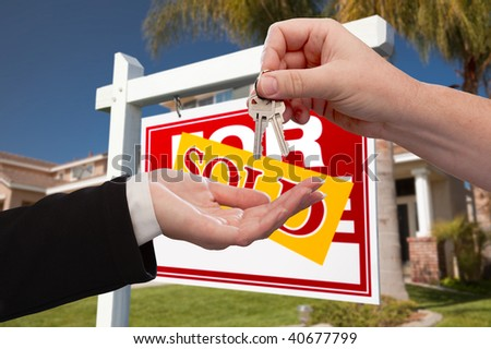 Agent Handing Over the Key to a New Home with Real Estate Sign and House in the Background. - stock photo