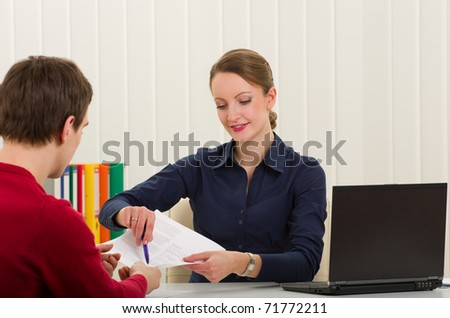 Agent (or notary public) holding pen pointing at signature place on a contract document to man - stock photo