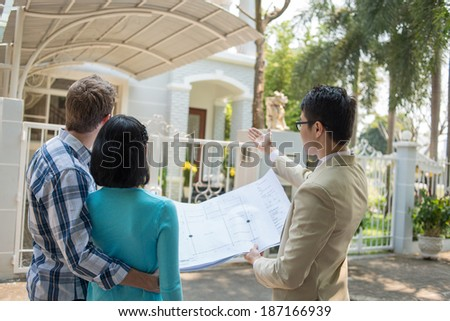 Agent showing a plan of the house to the young couple - stock photo