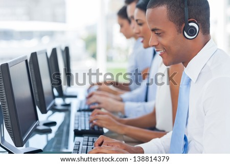Agent smiling while working on his computer with colleagues next to him - stock photo