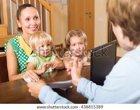 Agent talking with smiling mother and two little children about insurance - stock photo