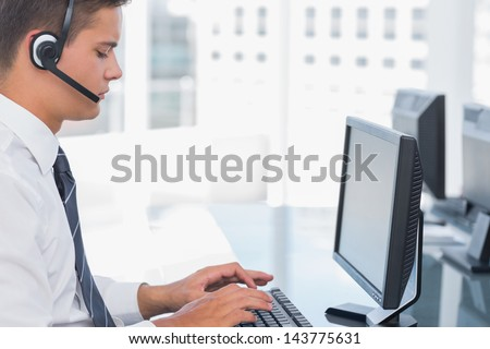 Agent working in a call centre and using his computer