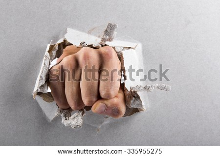aggression concept, wall is broken through by a fist - stock photo