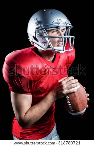 Aggressive American football player holding ball on black background - stock photo