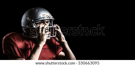 Aggressive American football player holding helmet against black